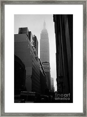 empire state building shrouded in mist in amongst dark cold buildings on 33rd Street new york city Framed Print by Joe Fox