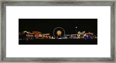 Ferris Wheel And Neon Signs Lit Framed Print by Panoramic Images