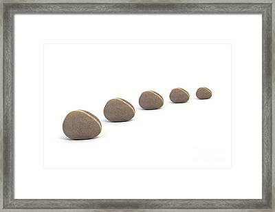 Five Queuing Pebbles Against White Background Framed Print by Natalie Kinnear
