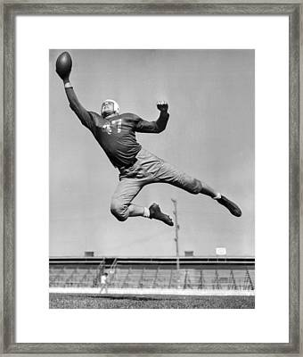 Football Player Catching Pass Framed Print by Underwood Archives