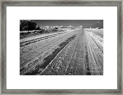 frozen salt and grit covered rural small road in Forget Saskatchewan Canada Framed Print by Joe Fox