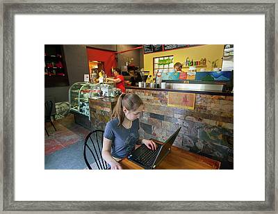 Girl Using A Laptop In A Cafe Framed Print by Jim West