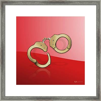 Gold Handcuffs On Red Background Framed Print by Serge Averbukh