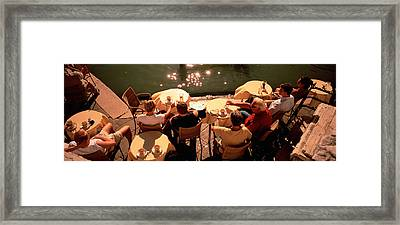 High Angle View Of Tourists Sitting Framed Print by Panoramic Images