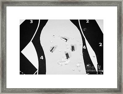 Human Shaped Target Ridden With Bullet Holes And 9mm Empty Shell Casings Framed Print by Joe Fox