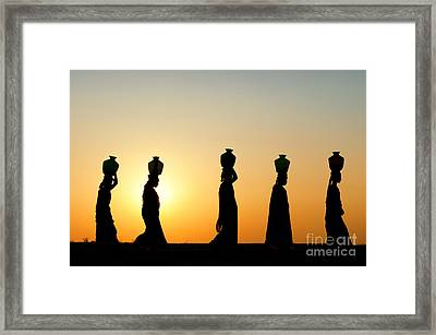 Indian Women Carrying Water Pots At Sunset Framed Print by Tim Gainey