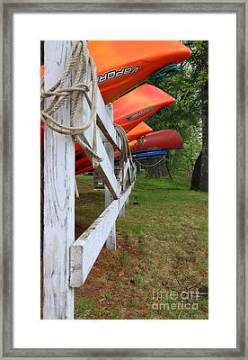 Kayaks On A Fence Framed Print by Michael Mooney