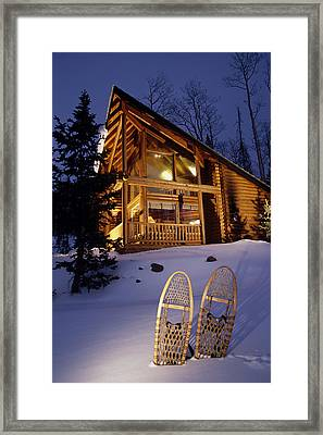 Lighted Cabin With Snowshoes In Front Framed Print by Michael DeYoung