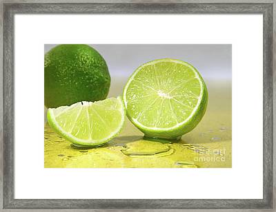 Limes On Yellow Surface Framed Print by Sandra Cunningham