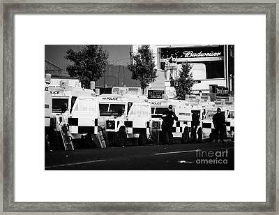 Line Of Psni Landrovers And Officers On Crumlin Road At Ardoyne Shops Belfast 12th July Framed Print by Joe Fox