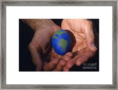 Man Holding Earth Egg Framed Print by Jim Corwin