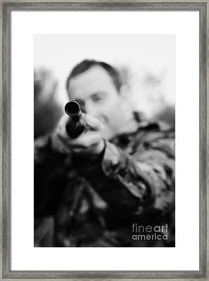 Man In Camouflage Clothes Takes Aim At Camera With Shotgun On December Shooting Day Framed Print by Joe Fox