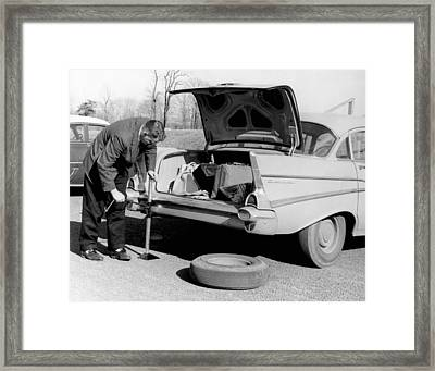 Man Jacking Up A Car Framed Print by Underwood Archives