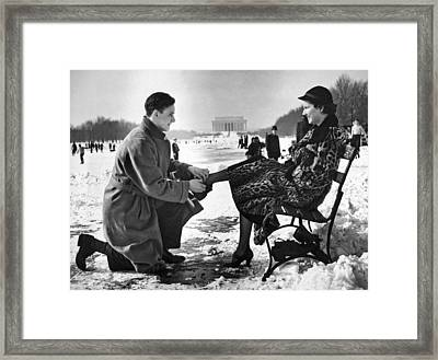 Man Lends A Helping Hand To Put On Skates Framed Print by Underwood Archives