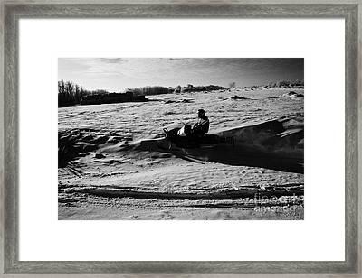man on snowmobile crossing frozen fields in rural Forget Saskatchewan Canada Framed Print by Joe Fox