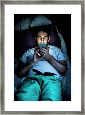Man Using Smartphone In Bed Framed Print by Samuel Ashfield