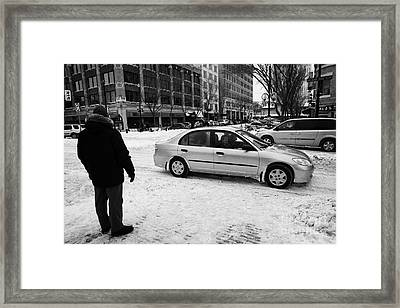 man watching car travelling along snow covered city streets in Saskatoon Saskatchewan Canada Framed Print by Joe Fox