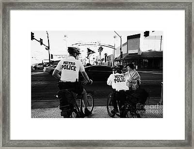 metro police bicycle cops help a tourist with directions in downtown Las Vegas Nevada USA Framed Print by Joe Fox
