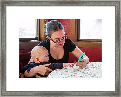 Mother And Baby Using A Mobile Device Framed Print by Jim West