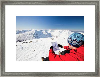 Mountaineer Checking His Map Framed Print by Ashley Cooper