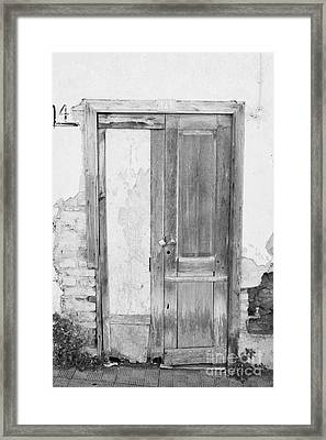 number 141 old weathered brown wooden door entrance to abandoned house with cracked stucco yellow walls in Tacoronte Tenerife Canary Islands Spain Framed Print by Joe Fox