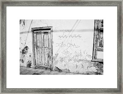 old weathered green painted wooden door entrance to abandoned house with cracked stucco walls and graffitti in Tacoronte Tenerife Canary Islands Spain Framed Print by Joe Fox
