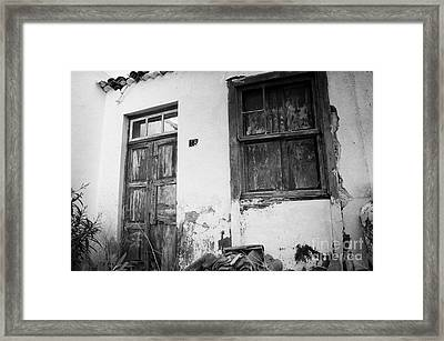 old weathered wooden door entrance to abandoned house 18 with window and cracked stucco walls in Los Banquitos Tenerife Canary Islands Spain Framed Print by Joe Fox