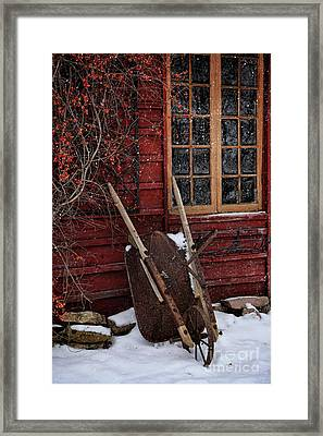 Old Wheelbarrow Leaning Against Barn In Winter Framed Print by Sandra Cunningham