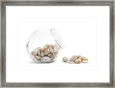 Pebbles And Glass Jar Against White Background Framed Print by Natalie Kinnear