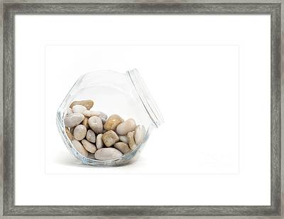Pebbles In A Glass Jar Against White Background Framed Print by Natalie Kinnear