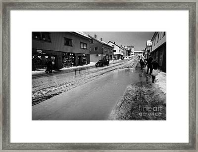 pools of thawing water from ice on main shopping street storgata Honningsvag finnmark norway europe Framed Print by Joe Fox