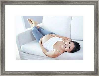 Pregnant Woman Lying On Sofa Framed Print by Ruth Jenkinson