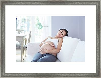 Pregnant Woman Sitting On Sofa Framed Print by Ruth Jenkinson