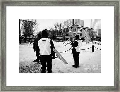 public workers clearing snow and ice off the sidewalks in downtown Saskatoon Saskatchewan Canada Framed Print by Joe Fox