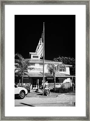 Raising The American Flag On A Flagpole Outside The Chamber Of Commerce Building In Key Largo Florid Framed Print by Joe Fox