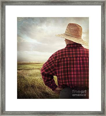 Rear View Of A Farmer Looking At His Land Framed Print by Sandra Cunningham