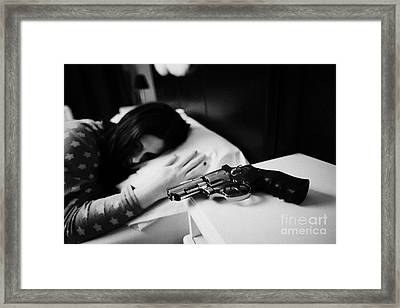 Revolver Handgun On Bedside Table Of Early Twenties Woman In Bed In A Bedroom Framed Print by Joe Fox