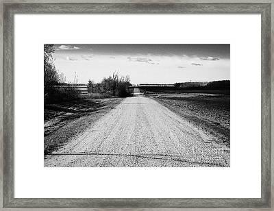 rough rural unpaved gravel road in remote Saskatchewan Canada Framed Print by Joe Fox