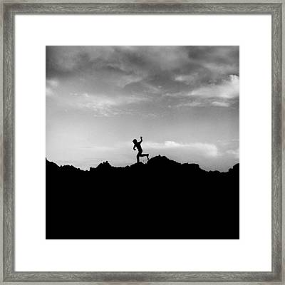 Running Boy Silhouetted Against Dramatic Sky Framed Print by Donald  Erickson