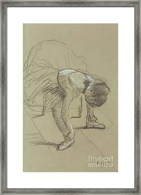 Seated Dancer Adjusting Her Shoes Framed Print by Edgar Degas
