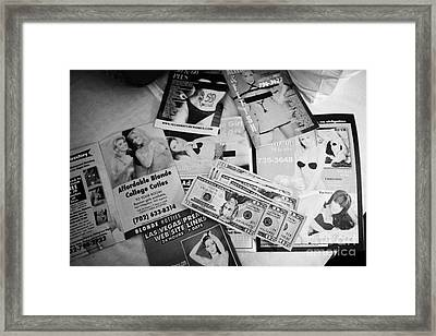 selection of leaflets advertising girls laid out on a hotel bed with us dollars cash in Las Vegas Ne Framed Print by Joe Fox