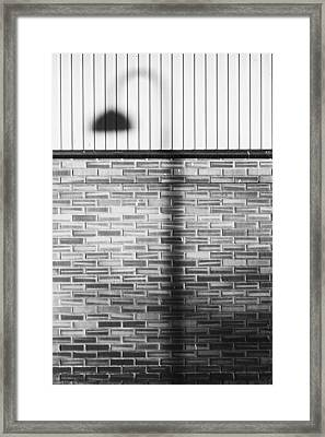 Shadow On The Wall Framed Print by Erik Brede