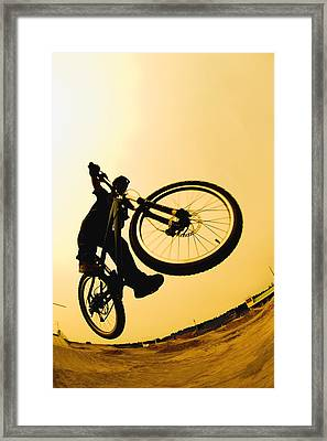 Silhouette Of A Cyclist Against A Framed Print by Corey Hochachka