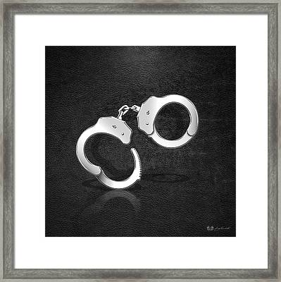 Silver Handcuffs On Black Leather Background Framed Print by Serge Averbukh