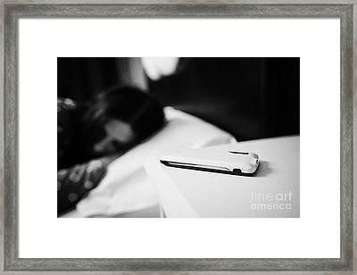 Smartphone On Bedside Table Of Early Twenties Woman In Bed In A Bedroom Framed Print by Joe Fox