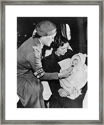 Stewardess Feeding Baby Framed Print by Underwood Archives