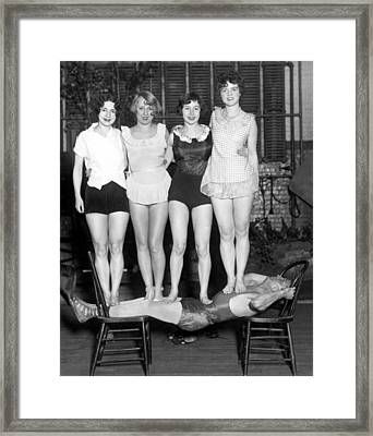 Strongman Holds Up Actresses Framed Print by Underwood Archives