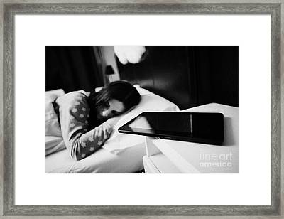 Tablet Computer On Bedside Table Of Early Twenties Woman In Bed In A Bedroom Framed Print by Joe Fox