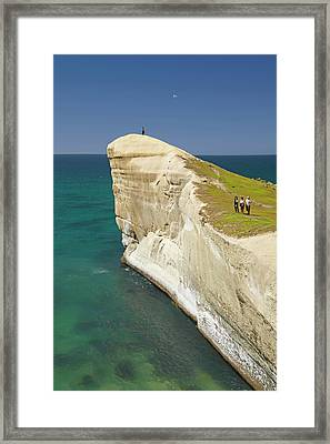 Tourists On Cliff Top At Tunnel Beach Framed Print by David Wall