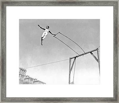 Trapeze Artist On The Swing Framed Print by Underwood Archives